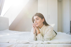 Woman lying on the bed and waking up in the morning Stock Photos
