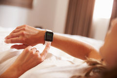 Woman Lying in Bed Whilst Checking News App on Smart Watch stock photography