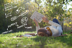Woman lying on bedding on green grass with ipad. Lying woman drawing business concept on tablet pc screen during rest in the park Royalty Free Stock Photo
