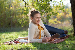 Woman lying on bedding on green grass with ipad Royalty Free Stock Photo