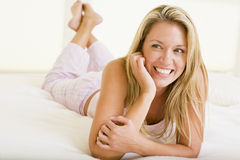Woman lying in bedroom smiling Royalty Free Stock Photo