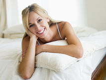 Woman lying in bedroom smiling Stock Photography