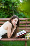 Woman lying on bench with book Royalty Free Stock Photos