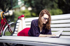 Woman lying on bench and read book Stock Photos