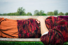 Woman lying on a bench relaxing Stock Image