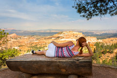 Woman lying on bench at the top of rocky mountain. Young woman lying on wooden bench on the top of rocky mountain in valley stock photography