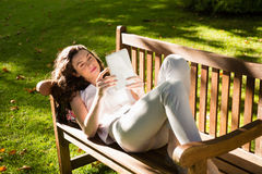 Woman lying on bench and using digital tablet in garden Royalty Free Stock Image