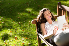Woman lying on bench and using digital tablet in garden on a sunny day Stock Images