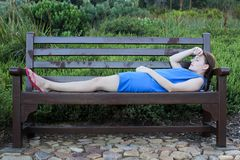 Woman lying on a Bench very tired Stock Images