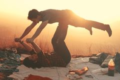 Woman Lying on Blanket Under Man on Her Legs Holding Hands during Golden Hour Royalty Free Stock Photos