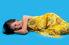 Woman lying on a blue background Stock Photos