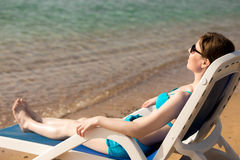 Woman lying on blue deckchair Royalty Free Stock Photos