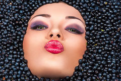 Woman lying in blueberries and sends an air kiss Stock Photography