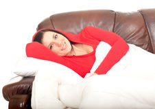 Woman lying on brown sofa under duvet Royalty Free Stock Photo