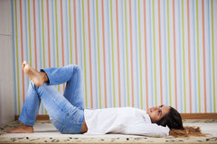 Woman lying in the carpet Stock Image