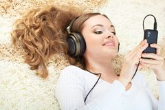 Woman lying on carpet and listening to music Royalty Free Stock Image