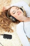 Woman lying on carpet and listening to music Royalty Free Stock Photography