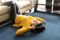 Woman Lying On Carpet And Listening To Music. Stylish woman in yellow sweater having fun while listening to songs on headphones at home royalty free stock image