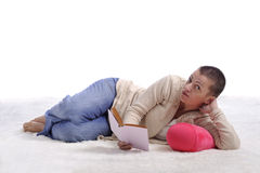 Woman lying on a carpet reading a book Royalty Free Stock Photo