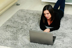 Woman lying on the carpet and using laptop Stock Image