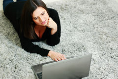 Woman lying on the carpet and using laptop Stock Photos