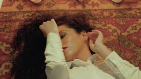 Woman is lying on the carpet. A young curly woman in white with beautiful red lips is lying on the carpet, her hands are touching her face. Valentine`s Day. Girl stock footage