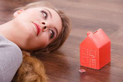 Woman lying with cash box. Home mortgage real estate property finances family concept. Woman lying with cash box. Young lady on floor next to piggy bank house Stock Photos