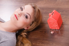 Woman lying with cash box. Home mortgage real estate property finances family concept. Woman lying with cash box. Young lady on floor next to piggy bank house Royalty Free Stock Photo