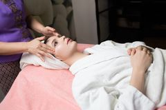 Woman lying with closed eyes and having face or head massage in spa. Young woman lying with closed eyes and having face or head massage in spa stock images