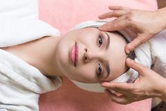 Woman lying with closed eyes and having face or head massage in spa. Young woman lying with closed eyes and having face or head massage in spa stock photo