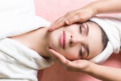 Woman lying with closed eyes and having face or head massage in spa. Young woman lying with closed eyes and having face or head massage in spa royalty free stock photo