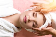 Woman lying with closed eyes and having face or head massage in spa. Young woman lying with closed eyes and having face or head massage in spa stock photos
