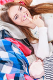 Woman lying on clothes with finger on lips. Royalty Free Stock Photos