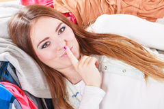 Woman lying on clothes with finger on lips. Stock Image