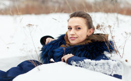 Woman lying in coat on  snow Royalty Free Stock Photo