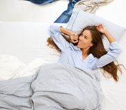Woman lying in comfortable bed smiling Stock Photography