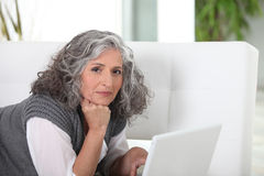 Woman lying on couch Stock Images