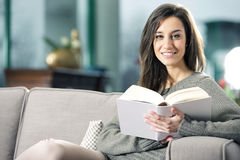 woman lying on couch with book Royalty Free Stock Photos