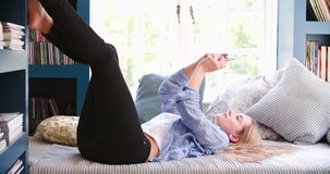Woman Lying On Couch In Home Office Using Mobile Phone. Young woman lying on couch using mobile phone in home office.Shot in 4k on Sony FS700 at frame rate of stock video