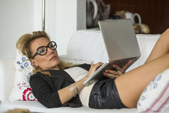 Woman lying on the couch with laptop. Stock Photos