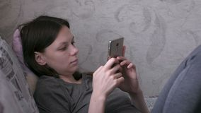 Woman lying on the couch and looking something at the mobile phone. Woman lying on the couch and looking something at the mobile phone stock footage