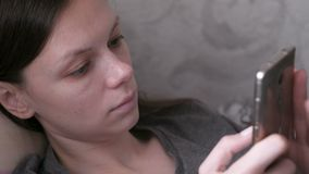 Woman lying on the couch and reading something at the mobile phone. Close-up face. Woman lying on the couch and reading something at the mobile phone. Close-up stock video