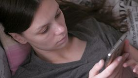Woman lying on the couch and reading something at the mobile phone. Close-up face top view. Woman lying on the couch and reading something at the mobile phone stock footage