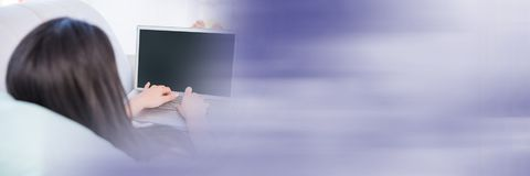 Woman lying on couch typing on laptop with blurry purple transition Royalty Free Stock Photos