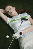 Woman Lying On Course With Golf Club And Ball. Thoughtful young woman lying on course with golf club and ball royalty free stock images