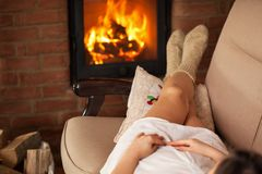 Woman lying in cozy warmth on a couch in front of fireplace Royalty Free Stock Photography