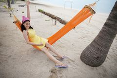 Woman lying on the cradle at the beach. Beautiful woman lying on the cradle at the beach by the sea royalty free stock photography
