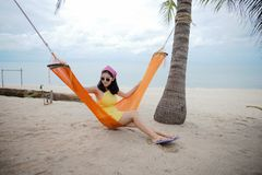 Woman lying on the cradle at the beach. Beautiful woman lying on the cradle at the beach by the sea royalty free stock photos