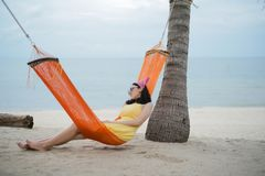Woman lying on the cradle at the beach. Beautiful woman lying on the cradle at the beach by the sea stock photo