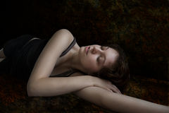 Woman lying in dark background Royalty Free Stock Images